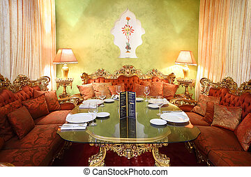 beautiful glass table with serving and red sofas in eastern...