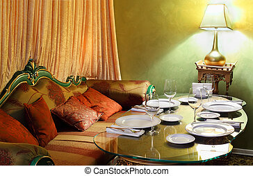 beautiful glass table with serving, lamp and sofa in eastern...