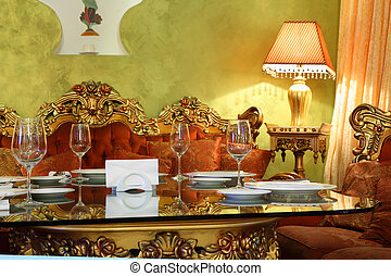 beautiful glass table with serving, carved red sofa in eastern luxury restaurant