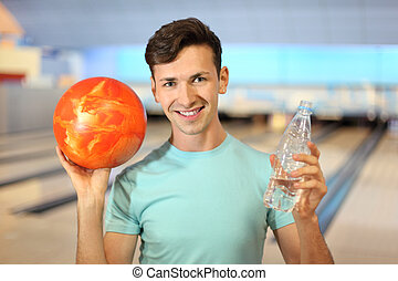 Young man holds orange ball and bottle with water in bowling club; shallow depth of field