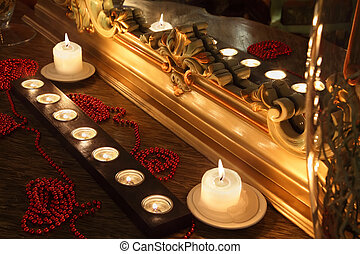 Burning candles and long red beads lie near mirror with gold carved frame