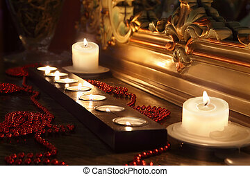 Burning candles and red beads lie near mirror with gold...