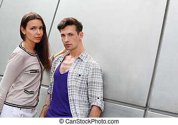Beautiful young man and brunette woman stand near gray wall; focus on man