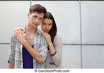 Beautiful man and woman stand near gray wall and look at camera; focus on girl