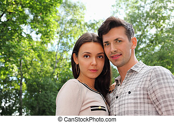 Beautiful man and woman stand in park; green trees and sunny day