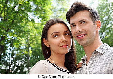 Beautiful smiling man and woman stand in park; green trees and sunny day; focus on girl