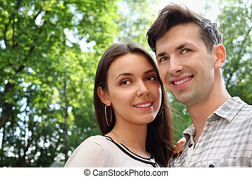 Happy man and woman stand in park; green trees and sunny day