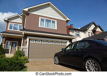 Car near the garage of new two-storied brown cottage with...