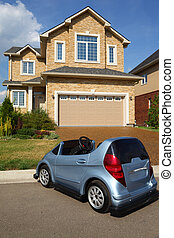 Little car near the garage of new two-storied beige stone cottage.