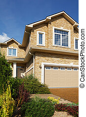 New two-storied beige stone cottage with garage and garden...