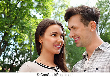 Happy man and woman stand in park and look at each other;...