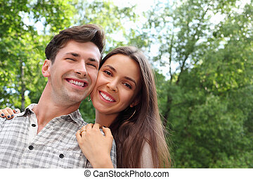 Happy man and woman stand in park; woman holds on shoulders of man; green trees and sunny day