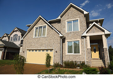 Low view of new two-storied beige stone cottage with yellow...