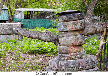 Corner of a green park for playing paintball with trees, concrete blocks, old abandoned bus, tires.