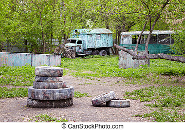 Corner of a green park for playing paintball with concrete blocks, old abandoned bus and lorry, tires.