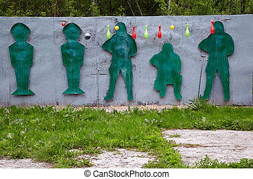 Shooting range for paintball players with figures and hanging objects