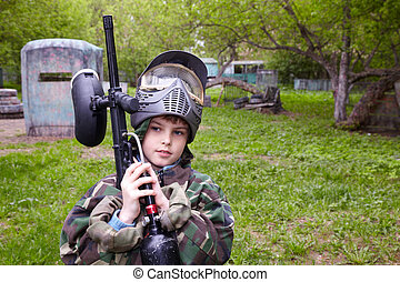 Boy in camouflage with marker for paintball stands at the paintball ground.