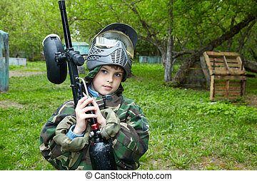 Boy in camouflage suit stands against the paintball area...
