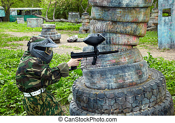 Paintball player dressed in camouflage and protective mask...