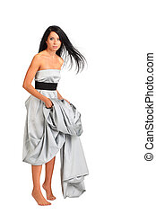 beautiful woman wearing long silver dress stands on tiptoe and holds hem isolated on white