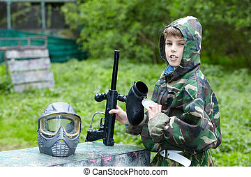 Boy in camouflage with removed protective mask holds a...