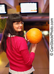 happy girl with yellow ball stands back to camera in bowling...