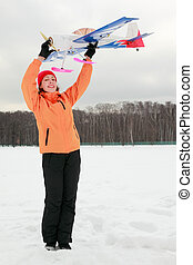 beautiful young woman in orange jacket played with airplane at winter outdoors