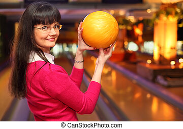 happy girl with yellow ball stands in bowling club and...