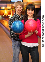 smiling young wife and husband with balls stand in bowling club