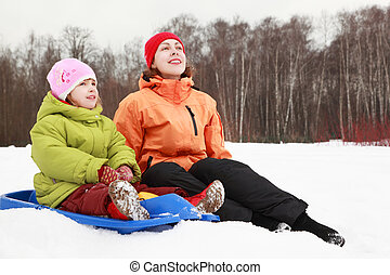 beautiful young mother and daughter sitting on snow and looking at sky in winter outdoors, focus on girl