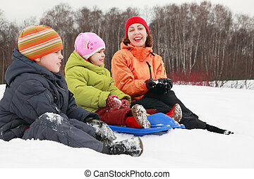 beautiful young mother, little son and daughter sitting on snow and smiling at winter outdoors, focus on girl