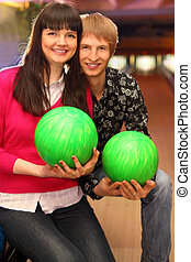 smiling young wife and husband with green balls sit in bowling club