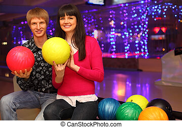 smiling young wife and husband with red and yellow balls sit in bowling club