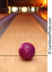violet sphere ball standing on long bowling lane before...