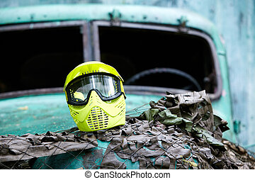 Yellow protective mask for paintball players lies on the hood of an old abandoned lorry without windshields, hood is covered with a scrim.