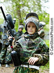 Boy in the camouflage suit holds a paintball gun barrel up ,...