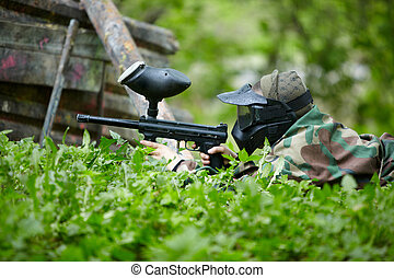 Paintball player in camouflage and protective mask with...