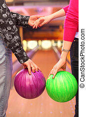 Female and male hands with balls in bowling club; man and...