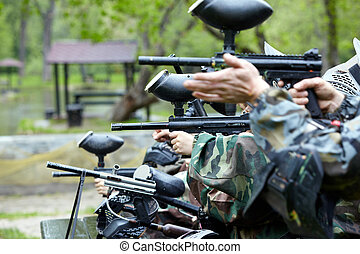 Hands of paintball players and gun, from wich they aims and...