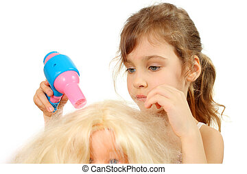 Little girl dries doll hair by bright toy hair dryer...