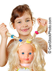 Little girl shows dolls braids, which herself braided isolated on white background