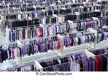 Big clothing store, many rows with hangers with skirts and...