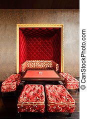 Beautiful red couch in niche, table and stools in empty...