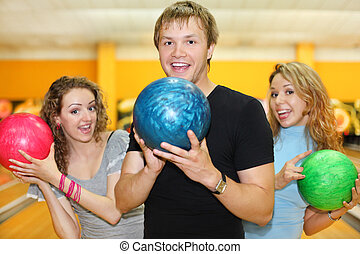 Young man and two happy beautiful girls hold balls in bowling club; focus on man