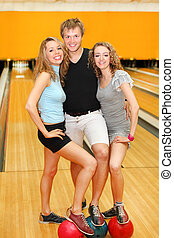 Young man and two happy beautiful girls put feet on balls in bowling club