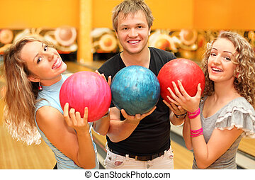 Young man and two happy beautiful girls made row of balls in bowling club; focus on man