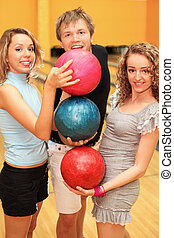 Young man and two happy beautiful girls made pyramid of balls in bowling club; focus on left woman