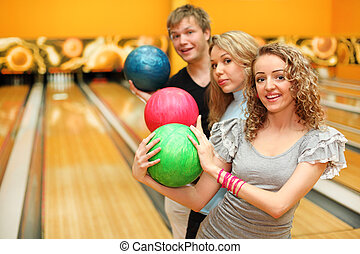 Young man and two happy beautiful girls made row of colorful balls in bowling club; focus on right woman
