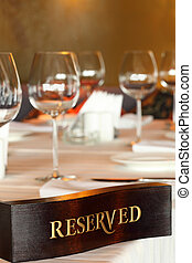 Wooden reserved plate on restaurant table with empty dishes...