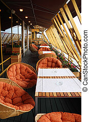 Row of origilal spherical wicker chairs and tables at...